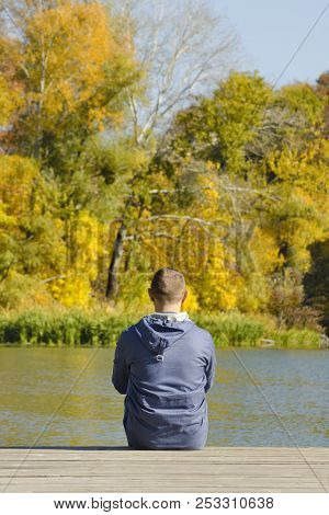 Young Man Sits On The Pier. Autumn Sunny Day. Back View