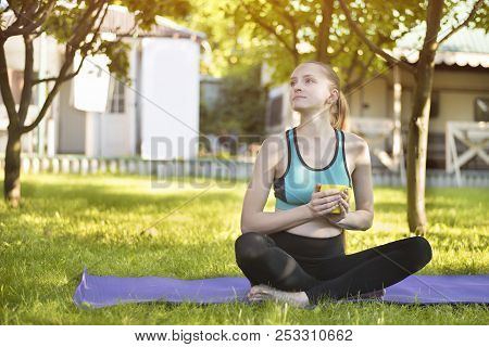 Beautiful Woman Sitting On Yoga Mat With Cup Of Tea. Summer Morning In The Garden.