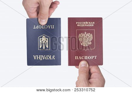 Ukrainian And Russian International Passports In The Man's Hand. White Background. Close Up