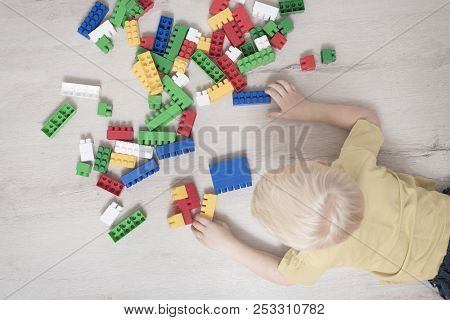 Blond Boy Lies On The Floor Among The Constructor. Top View