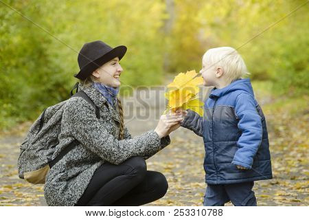 Blond Boy Gives His Mother A Bouquet Of Yellow Leaves. Autumn Forest