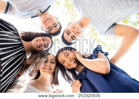 Low Angle View Of Group Of Teenagers Standing In A Huddle With Their Heads Touching And Looking At C