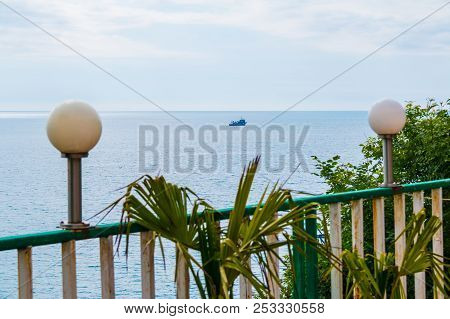 Lampposts On Railing And Leaves Of Palm Closeup On The Background Of Sea With The Fishing Ship