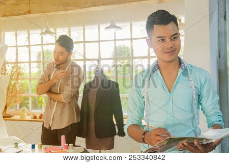 Young Asian Male Desiner Standing With Desiner Team Working In The Studio.