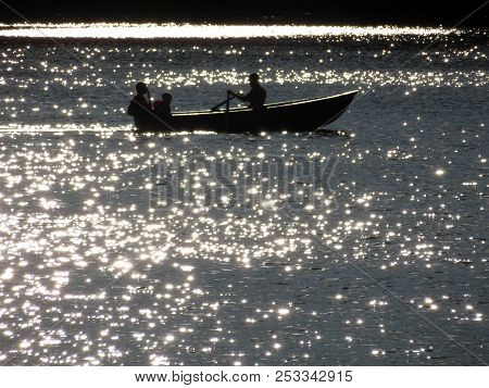 Silhouette Of A Rowing Boat With People On A Shimmering Water In Sunshine. Family Sailing On A Rowin