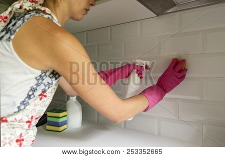 Woman Cleaning Kitchen Tiles With Spray Cleaner And Sponge. Household Equipment, Spring-cleaning, Ti