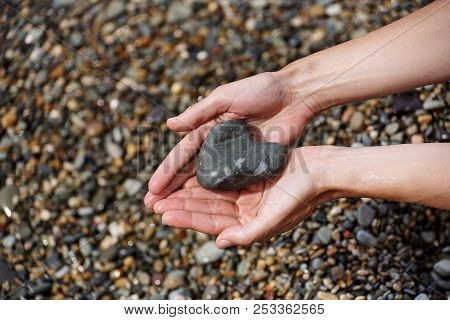 Wet Female Hands With A Stone In The Form Of A Heart Against A Background Of Wet Pebbles On The Beac