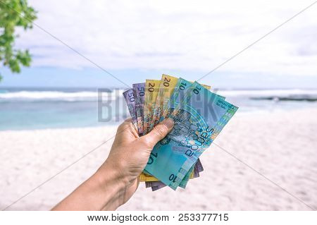 Samoan Tala Currency (wst) - Left Hand Holding Colorful Bank Notes From Western Samoa Against Backdr