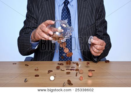 Photo of a banker sat at his desk emptying coins from his piggy bank.