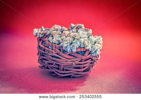 Pile Stones Of Raw Turquoise In Small Wooden Nest On A Wine Red Background. Blue And Green Color Sto