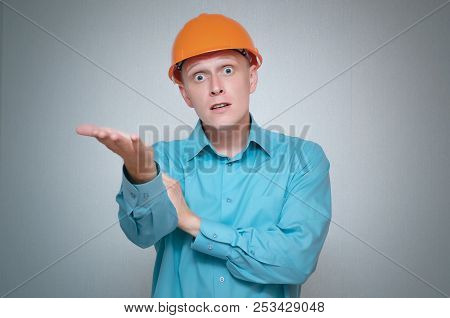 Perplexed builder worker isolated on gray background. poster