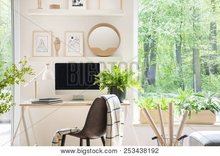 Shelves With Illustrations Above A Wooden Desk With Computer By A Window In A Natural, White Home Of