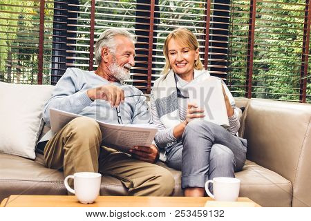 Senior Couple Relax Talking And Reading Newspaper Together On Sofa In Living Room At Home.retirement