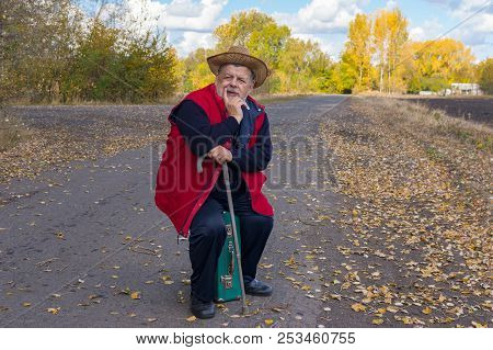 Senior Hiker With Walking Stick Sitting On An Old Green Suitcase On The Roadside While Waiting For B