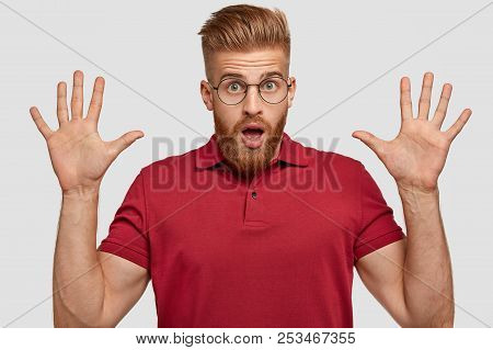 Horizontal Shot Of Terrible Unshaven Ginger Male With Stunned Expression, Keeps Palms Raised, Gestur