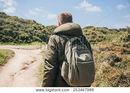 A Tourist With A Backpack Or Traveler Walks Through The Hilly Terrain.