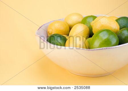 Bowl Of Lemons And Limes On Yellow.