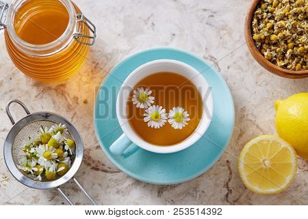 Chamomile flowers and chamomile tea. Chamomile tea in cup with flowers and lemon, close-up.