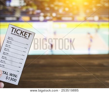 Bookmaker Ticket On The Background Of A Tv On Which Show Volleyball, Sports Betting, Volleyball