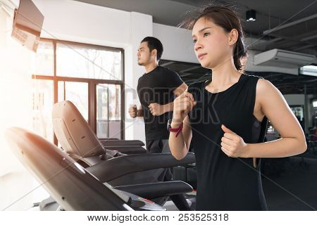 Running On Treadmills, Active Young Woman And Man Running On Treadmill In Gym