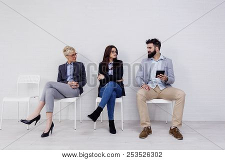 Three People Talking To Each Other While Waiting For Job Interwiev
