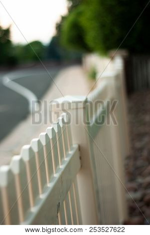 A White Picket Fence Stands Along A Sidewalk In A Suburban Neighborhood.