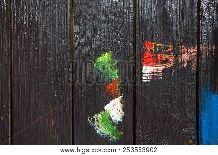 On A Wooden Background, Which Is Painted With Black Paint Painted With Different Colors Of Paint Sme
