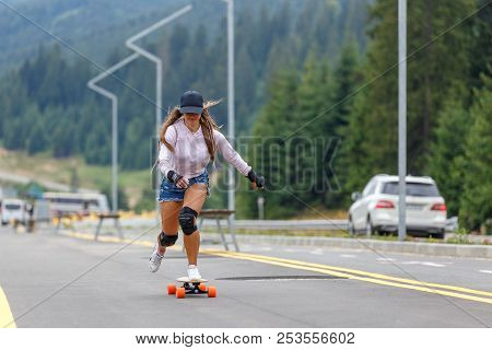 Young Girl Longboarding Downhill On Hillside Road
