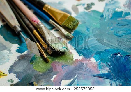 Artist Paint Brushes On Wooden Palette. Texture Mixed Oil Paints In Different Colors. Instruments To