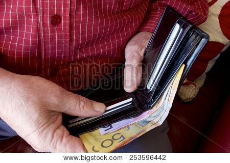 A Man Paying Money From His Wallet.