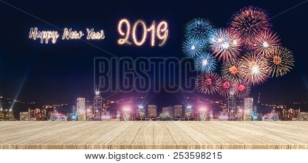 Happy New Year 2019 Fireworks Over Cityscape At Night With Empty Wood Plank Table Top,mock Up Templa