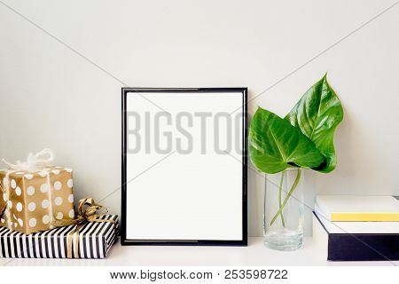 Black Photo Frame, Green Plant In A Chrystal Vase, Gift Boxes And A Pile Of Books Arranged Against E