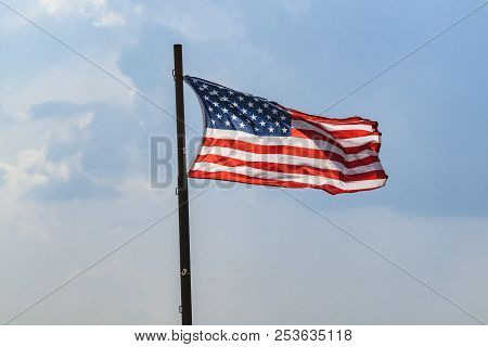 The Flag Of Usa On A Flagpole Waving In The Wind On A Blue Sky
