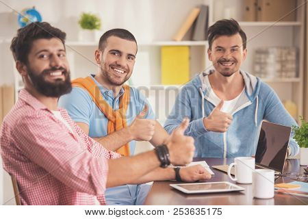 Three Young Smiling Men In Room With Laptop. Friendship Concept. Man Using Digital Device. Men With