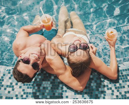 Top View. Smiling Couple In Swimming Pool In Summer. Leisure In Summer. Relaxation For Family Outdoo