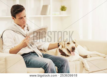 Young Man Sitting On White Sofa With Dog At Home. Reading Newspaper. Rest At Home. Relaxation Concep