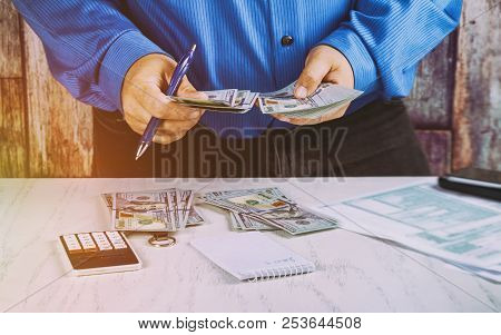 Hands Counting The Money In 100 Bills. Us Dollar Bills