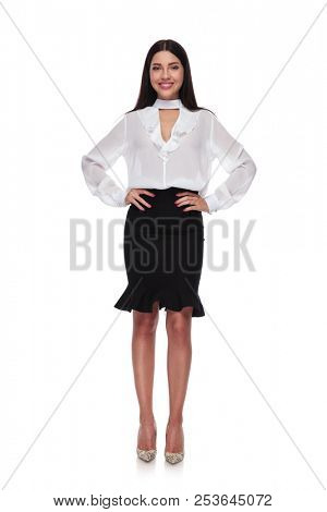 beautiful and confident businesswoman standing on white background while holding her hips, full body picture