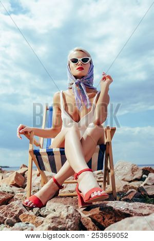 Bottom View Of Elegant Attractive Girl In Retro Swimsuit Sitting In Beach Chair