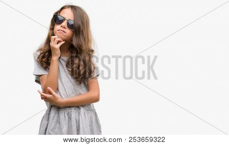 Brunette hispanic girl wearing sunglasses with hand on chin thinking about question, pensive expression. Smiling with thoughtful face. Doubt concept.