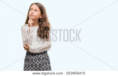 Brunette hispanic girl with hand on chin thinking about question, pensive expression. Smiling with thoughtful face. Doubt concept.