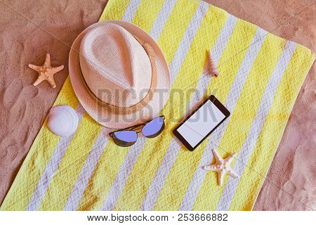 Hat, Smartphone And Sunglasses On Towel On Sand Beach
