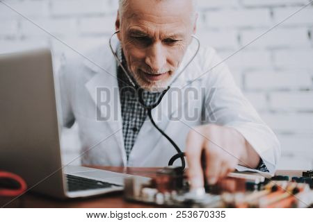 Computer Doctor In White Uniform With Stethoscope. Man With Motherboard. Examination Of Didital Devi