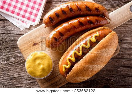 Delicious Grilled Smoked Sausages On A Roll With Yellow Mustard.