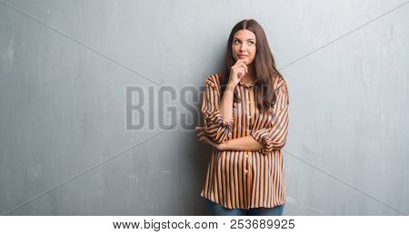 Young brunette woman over grunge grey wall with hand on chin thinking about question, pensive expression. Smiling with thoughtful face. Doubt concept.