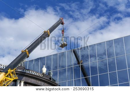 Telescopic Boom Of A Construction Crane Lifts The Load Against The Mirror Wall Of The Building Refle