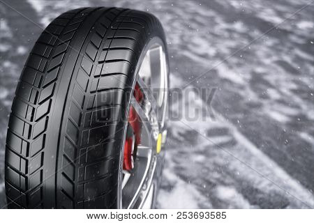 Car Wheel, Car Tire Standing On A Road. Concept Winter Tyres. Winter Tires With Snowy Background. Ca
