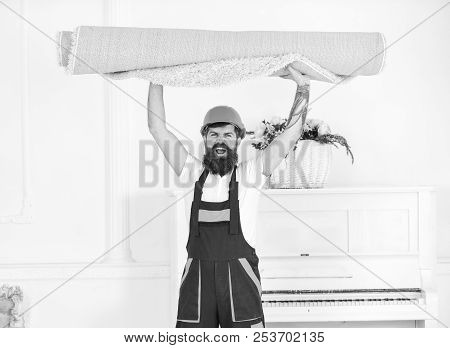 Loader wrapped carpet into roll. Relocating concept. Courier delivers furniture in case of move out, relocation. Man with beard, worker in overalls and helmet carries rolled carpet, white background. poster