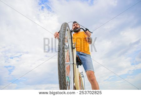 Bike Wheels Buying Guide. Man Bearded Hipster Rides Bicycle Bottom View Sky Background. Bike Mechani