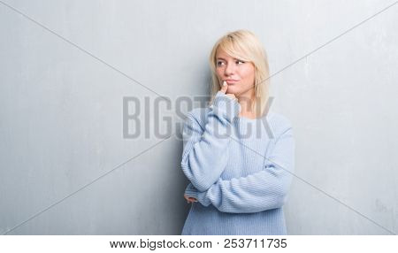 Adult caucasian woman over grunge grey wall wearing winter sweater with hand on chin thinking about question, pensive expression. Smiling with thoughtful face. Doubt concept.